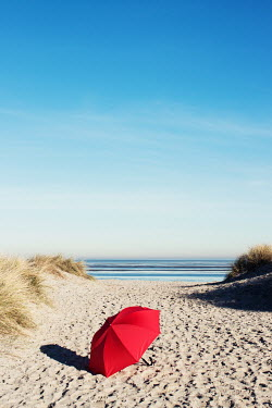 Manuela Deigert RED UMBRELLA ON SANDY BEACH Seascapes/Beaches