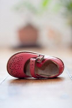 Lee Avison CHILD'S RED SHOE ON FLOOR INDOORS Miscellaneous Objects