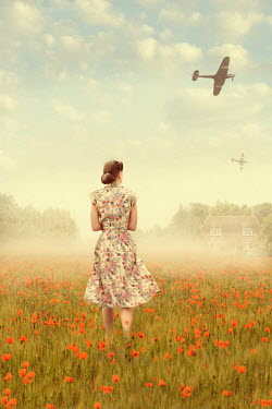Lee Avison 1940s woman walking in a poppy meadow with spitfire airplanes overhead Women