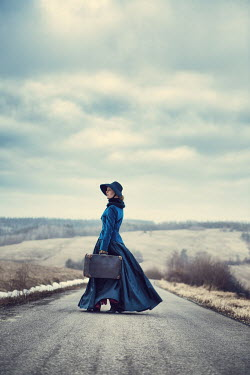 Magdalena Russocka victorian woman with suitcase on country road