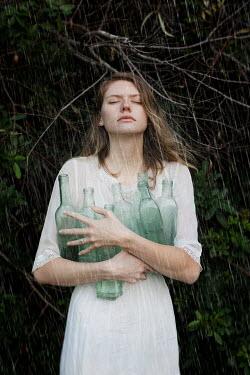 Erika Masterson WOMAN HOLDING BOTTLES OUTDOORS IN RAIN Women