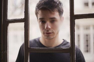 Anna Rakhvalova MAN OUTSIDE WINDOW LOOKING AT CAMERA Men