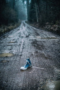 Magdalena Russocka blue sneaker abandoned on muddy road in forest