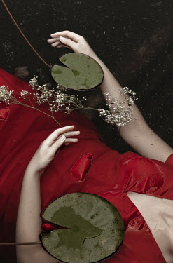 Monia Merlo WOMAN LYING IN POND WITH PLANTS Women
