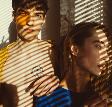 Marta Syrko TEENAGE COUPLE BY BLINDS IN SUNLIT WINDOW Couples