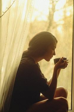 Maria Yakimova ASIAN WOMAN DRINKING COFFEE BY WINDOW Women