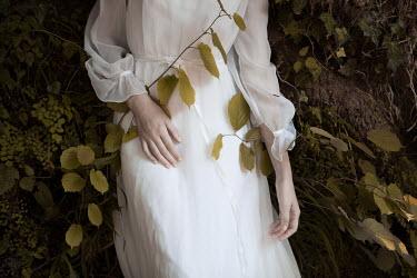 Monia Merlo WOMAN IN WHITE WITH PLANTS IN GARDEN Women