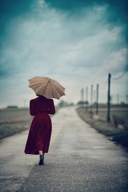 Magdalena Russocka woman with umbrella on country road Women