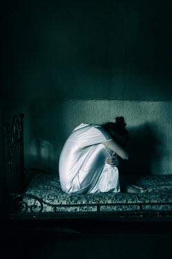 Magdalena Russocka sad girl sitting on bed in fetal position Women