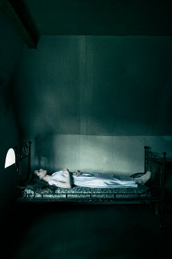 Magdalena Russocka eerie girl lying on bed in attic Women