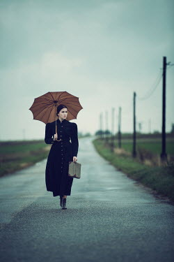 Magdalena Russocka woman with umbrella and suitcase on country road Women