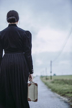 Magdalena Russocka woman with suitcase on country road Women