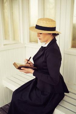 Nic Skerten HISTORICAL WOMAN SITTING AND WRITING ON PIER Women