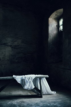 Magdalena Russocka empty derelict room with white dress lying on bench