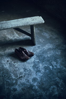 Magdalena Russocka wooden bench and worn man's hoes in derelict room