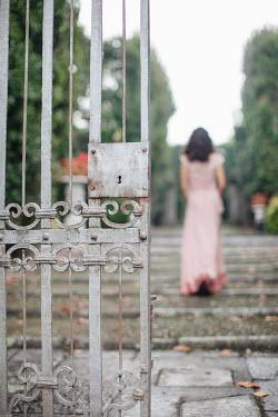 Nikaa WOMAN WALKING IN GARDEN WITH OPEN GATE Women