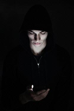 Magdalena Russocka teenage boy looking at cell phone in the shadows
