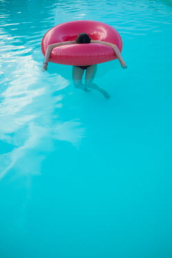Colin Hutton WOMAN FLOATING IN RUBBER RING IN POOL Women
