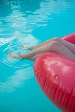 Colin Hutton FEMALE FEET AND RUBBER RING FLOATING IN POOL Women