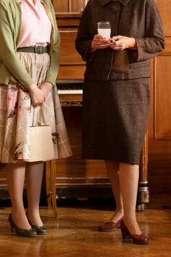 Colin Hutton TWO RETRO WOMEN STANDING NEAR PIANO Women