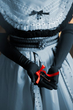 Ildiko Neer Victorian woman holding a key with red ribbon