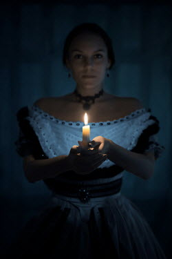 Ildiko Neer Victorian woman in blue ball gown holding a candle