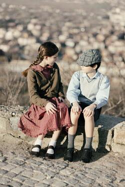 Krasimira Petrova Shishkova vintage boy and girl sitting on stone wall