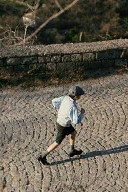 Krasimira Petrova Shishkova vintage boy running on cobbled street