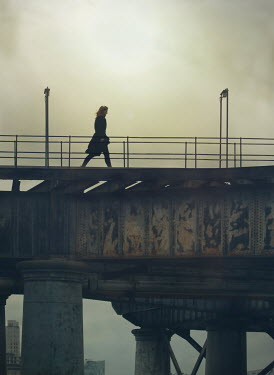 Mark Owen WOMAN WALKING ACROSS URBAN BRIDGE Women