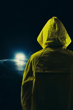 Magdalena Russocka modern man in yellow raincoat looking at car on road at night