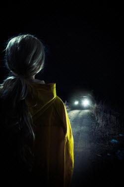 Magdalena Russocka modern woman in yellow raincoat looking at car on road at night