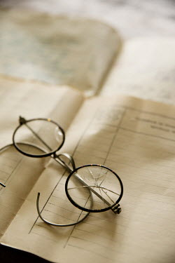 Maria Petkova broken glasses lying on documents Miscellaneous Objects