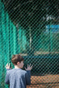 Galya Ivanova BOY HOLDING FENCE FROM BEHIND Children