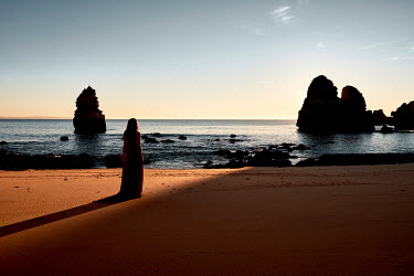 Chris Reeve WOMAN WAITING ON SANDY BEACH AT DUSK Women