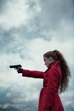 Magdalena Russocka modern woman pointing gun under stormy sky