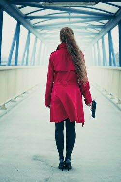 Magdalena Russocka modern woman holding gun on footbridge