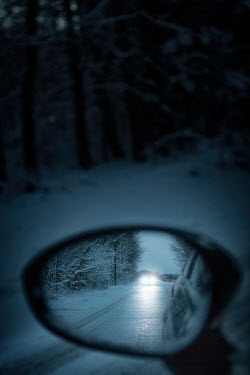 Magdalena Russocka car with headlights on rural road reflected in car wing mirror
