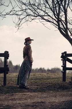 Magdalena Russocka historical woman in cowboy hat standing at fence