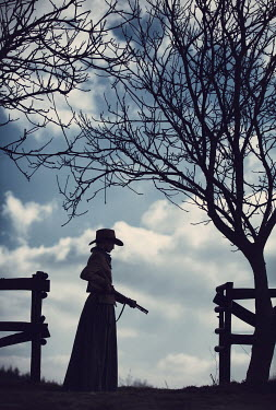 Magdalena Russocka silhouette of historical woman in cowboy hat with gun outside