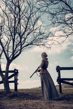 Magdalena Russocka historical woman with gun standing at fence