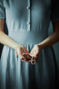 Ildiko Neer Vintage woman holding pearl necklace