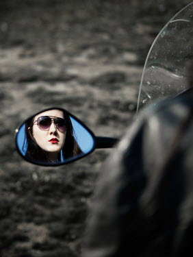 Magdalena Russocka modern woman's face reflected in motorcycle's mirror