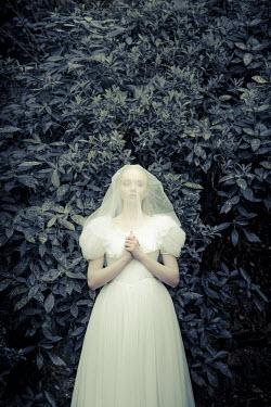 Nic Skerten UNSMILING BRIDE STANDING IN GARDEN Women