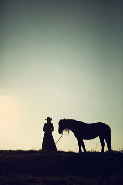 Magdalena Russocka historical woman in cowboy hat with horse at sunset