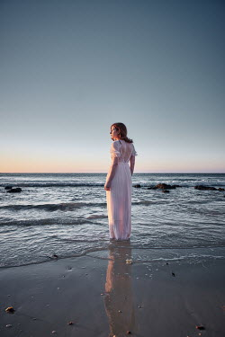 Chris Reeve WOMAN STANDING IN SEA AT SUNSET Women