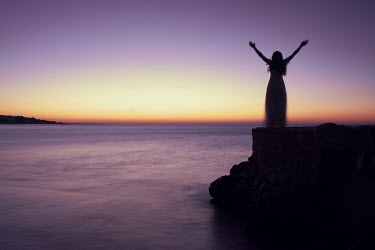 Chris Reeve WOMAN WITH STRETCHED ARMS STANDING ON ROCK BY SEA Women