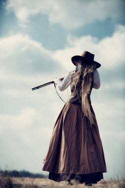 Magdalena Russocka historical woman in cowboy hat aiming with gun in field Women