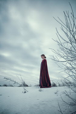 Magdalena Russocka historical woman in red cloak standing in snowy field