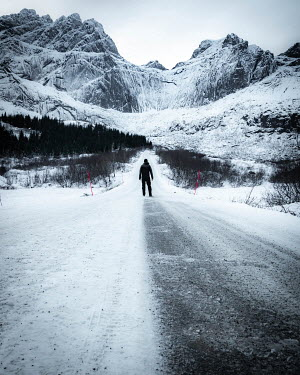 Paul Sheen MAN STANDING ON ROAD WITH ICY MOUNTAINS Men