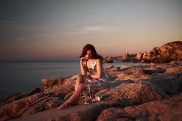 Chris Reeve THOUGHTFUL WOMAN ON ROCKY BEACH AT SUNSET Women